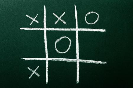 Tic-Tac-Toe game on green blackboard photo