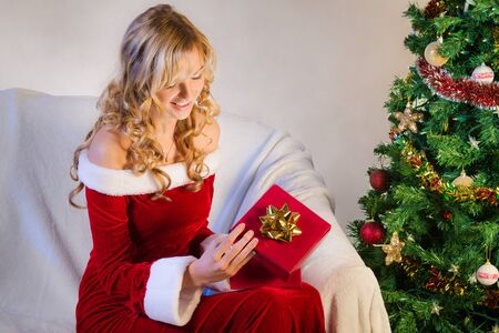 Beautiful young woman opening christmas gift photo