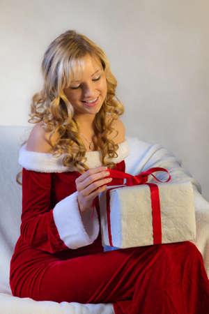 uitpakken: Jonge vrouw in het rood pak kerstmis gift