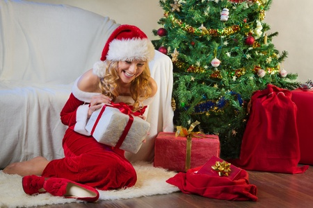 Beautiful woman in red enjoying christmas present photo