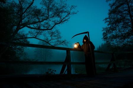 Man with scythe and oil lamp looks like death photo