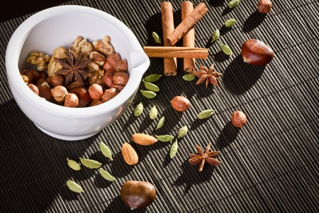 Different kinds of nuts in white mortar photo