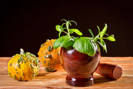 Fresh spices in wooden mortar with orange pumpkins photo