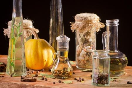 dried spice: Especias y una botella de aceite en tabl�n de madera Foto de archivo