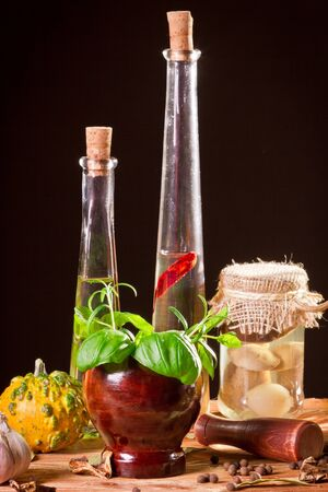 Bottle with vegetable oil and fresh spices in wooden shelf photo