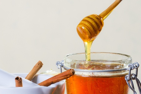Honey dipper with jar on white background photo