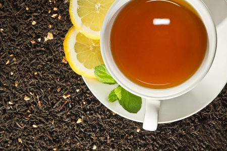 Hot cup of tea and fresh leaves on grain background photo