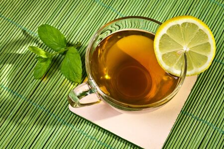 Hot cup of tea with lemon on bamboo mat photo