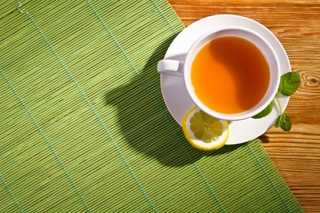 Hot tea with fresh leves and lemon on bamboo mat photo