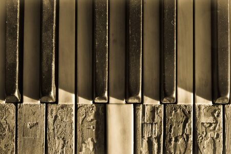 Closeup broken piano keys in sepia toned photo