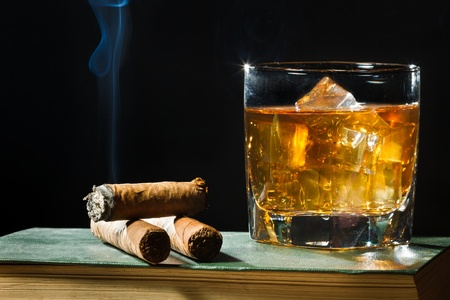 Tree cigar and whisky with ice in glass photo