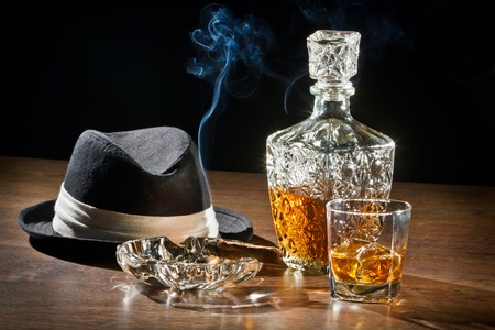 Retro scene, hat, smoking cigar and whisky with carafe