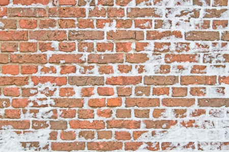 the red wall: Old snowy wall made from red brick Stock Photo