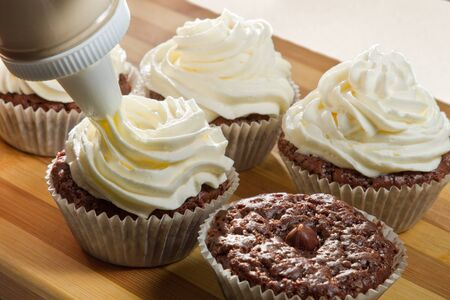 Decorating chocolate muffin with vanilla cream photo