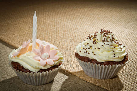 Two chocolate muffin with candle and vanilla cream photo