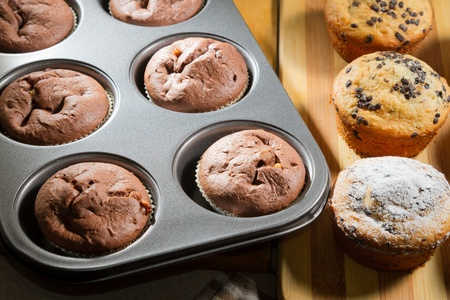 Vanilla and chocolate muffins in baking tray photo
