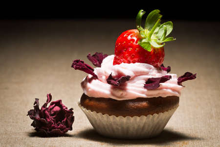 Muffin with strawberry and petals rose photo