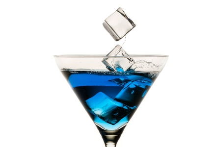 Dropping ice cubes into martini glasses on white background photo