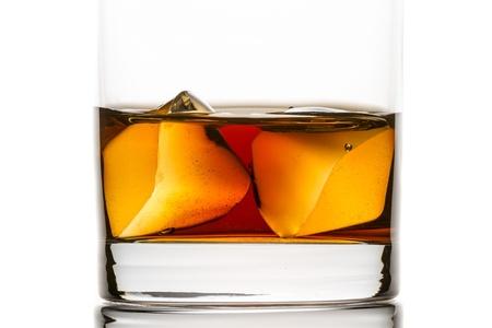 Primer whisky con cubitos de hielo en el fondo blanco