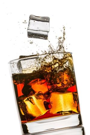 Splash en un vaso de whisky en el fondo blanco