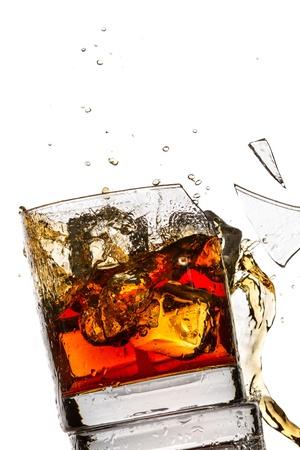 Los cubos de hielo rompiendo vaso de whisky lleno de bourbon en el fondo blanco