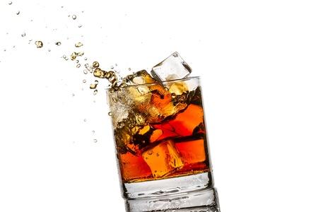 Splash en el vaso con cubitos de whisky y el hielo en el fondo blanco