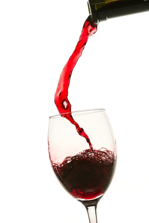 Pouring red wine into glass from bottle on white background Stock Photo - 12853333
