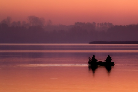 Silhouette of a fisherman catching fish in the boat at sunset Stock Photo - 13011389
