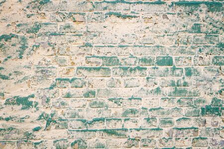 Old brick wall with peeling paint photo