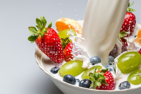 Splash of milk pushes fresh fruit from the bowl photo
