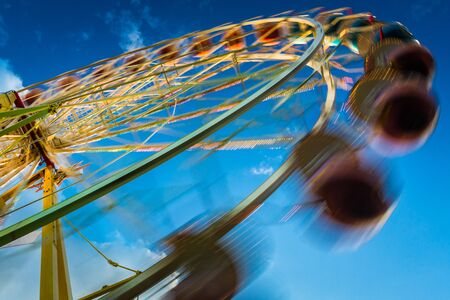 blurr: Blurry ferris wheel in motion on blue sky background