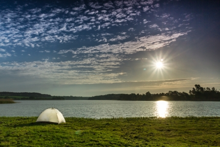 White tent, sun and clounds on the lake in summer