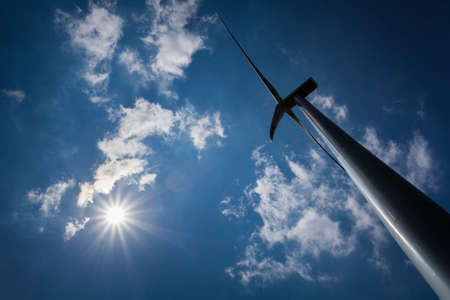 Wind Turbine with path on green field with blue sky photo