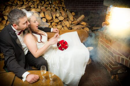 Surprised young couple sitting in front of a smoking fireplace Stock Photo - 14119488