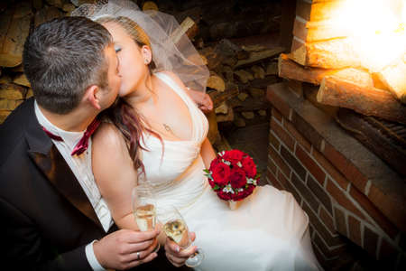 Happy just married couple sitting in front of the fireplace photo