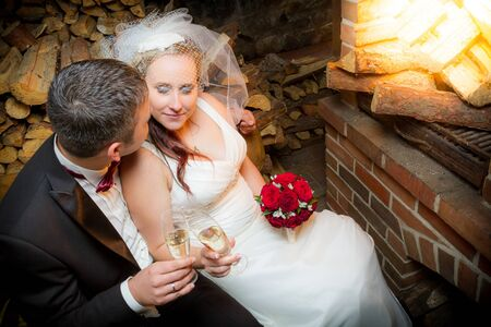 Young couple celebrating marriage in front of the fireplace photo