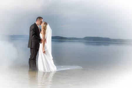 young couple kissing: Young couple kissing by the lake Stock Photo