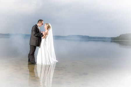 Young couple in the fog on the lake photo