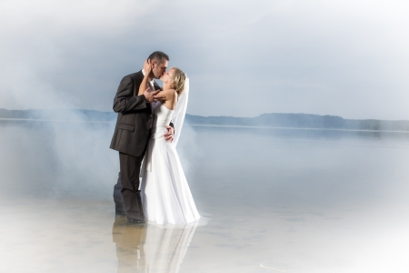 Just married young couple in a misty lake photo
