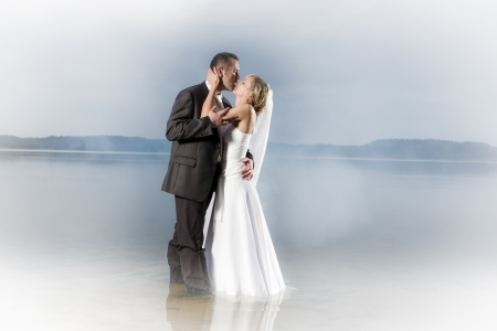 Young couple in a misty lake in a passionate kiss photo
