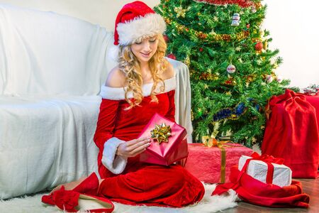 Beautiful woman opening a Christmas gift photo