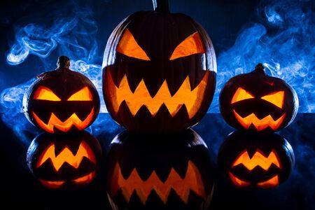 jack o latern: Three halloween pumpkins in the smoke background Stock Photo