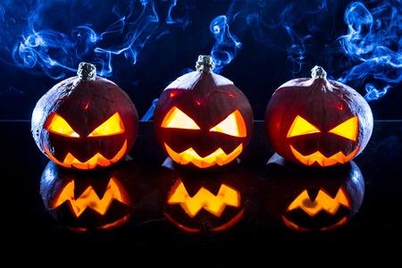 jack o latern: Three smoking pumpkins on black background Stock Photo
