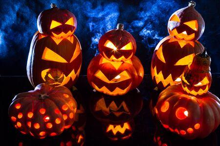 jack o latern: Group strange pumpkins on black background with smoke Stock Photo