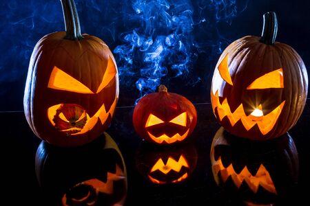 jack o latern: Three pumpkins and smoke on Halloween