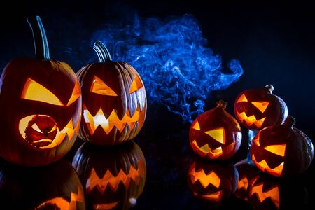 jack o latern: Small and large pumpkins for Halloween with candles on a black background Stock Photo