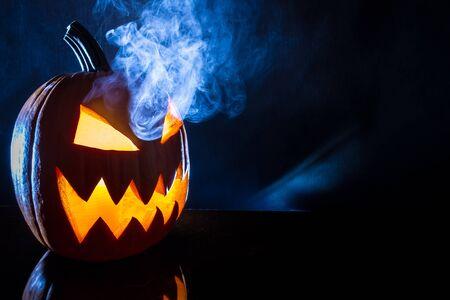 jack o latern: Smoking pumpkin with candle on Halloween Stock Photo