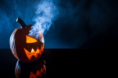 jack o latern: Smoking pumpkin with candle on Halloween on a black background
