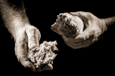sharing food: Human hand sharing with bread as charitable action