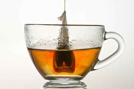 warm water: Theezakje in een kop gevuld met heet water op een witte achtergrond Stockfoto